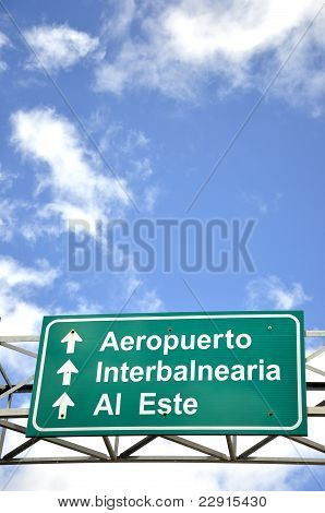 Freeway signs directing drivers under the blue sky with clouds