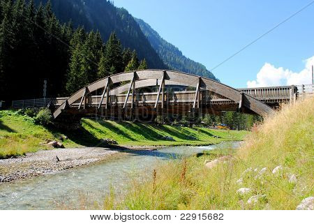 wooden bridge over small river in mountain landscape