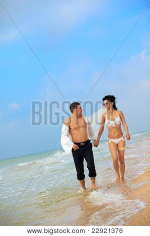Bride and groom running in sunshine on a beautiful tropical beach