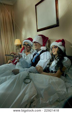 Gerente con dos sus subordinados viendo la televisión en la noche de año nuevo