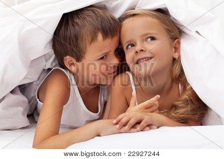 Kids planning the next prank hidden under the quilt