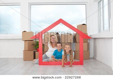 New home concept - people in empty room with cardboard boxes and house shaped frame