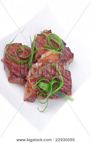 roasted beef meat strips steak on white ceramic plate isolated over white background