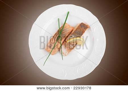 healthy fish cuisine : baked pink salmon steaks with green onion and lemon on white dish isolated over white background