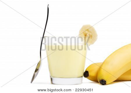 banana milkshake with a piece of banana a spoon and bananas aside