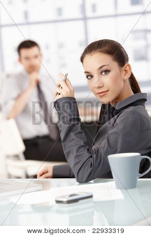 Portrait of young attractive businesswoman sitting at desk in office, smiling, man in the background.?