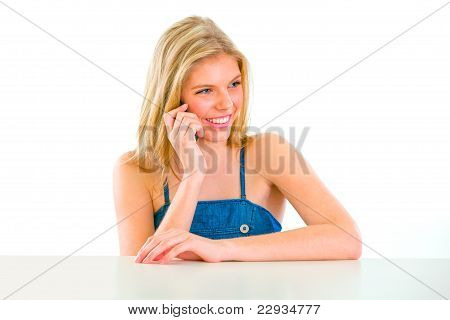 Smiling Teenager Sitting At Table And Talking Mobile