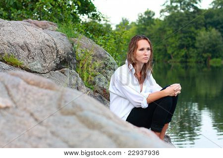 A Lonely Young Woman Sitting On Rocks On The River