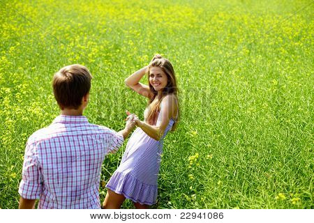 Portrait of happy young couple holding by hands in flower field