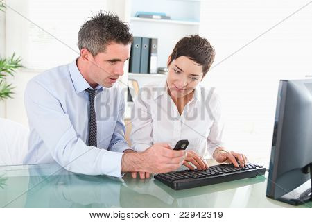 Man Showing Something To His Coworker On A Cellphone