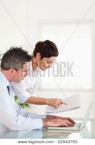 Portrait Of Colleagues Comparing A Blueprint Folder To An Electr