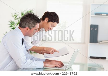 Coworkers Comparing A Blueprint Folder To An Electronic One