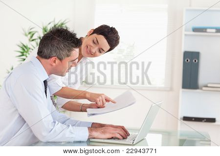 Office Workers Comparing A Blueprint Folder To An Electronic One