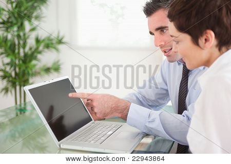Manager Pointing At Something To His Secretary On A Notebook