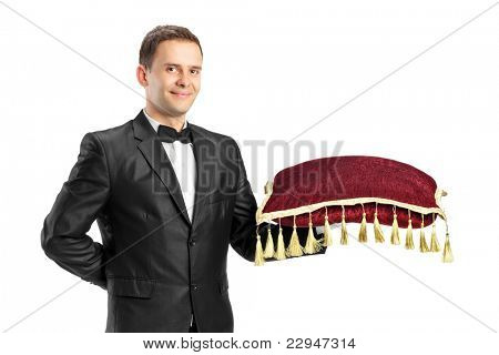 Man in a black suit with bow tie  holding a pillow isolated on white background