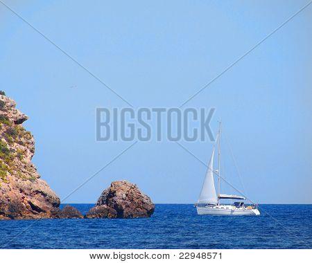 yacht near rocks