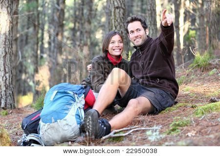 Young happy couple hiking in forest. Smiling couple resting enjoying a break during hike vacations. Caucasian man model. Asian woman model.