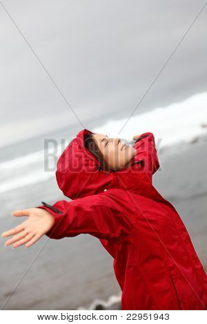 fall woman in rain happy by ocean. Woman enjoying rainy grey autumn day by the sea. Happy asian caucasian woman outdoor.