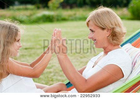 Happy childhood - girl with mother playing in colorful hammock