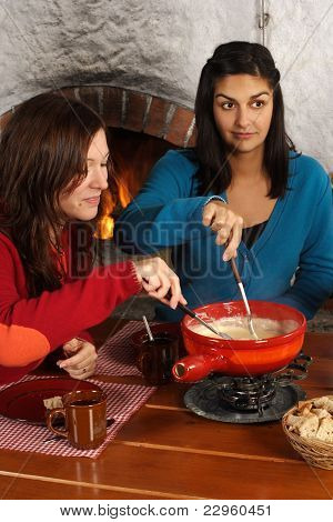 Women Dipping Bread Into Fondue