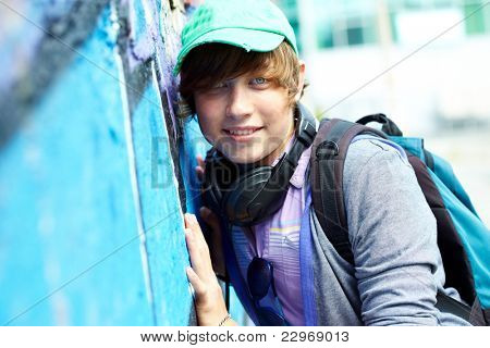 Portrait of teenage boy with backpack looking at camera