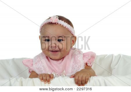 Cute Baby Girl In Pink Smiling In Crib