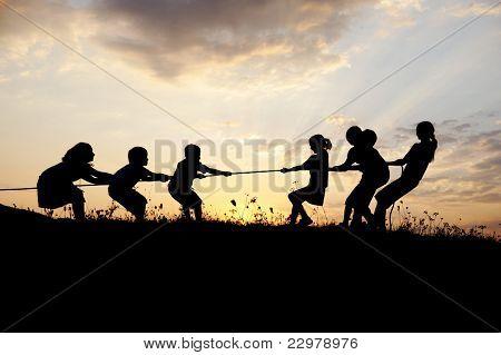 Silueta, grupo de niños felices jugando en el Prado, puesta de sol, verano