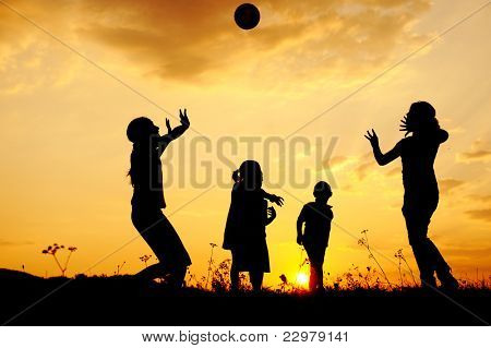 Silhouette, group of happy children playing on meadow, sunset, summertime