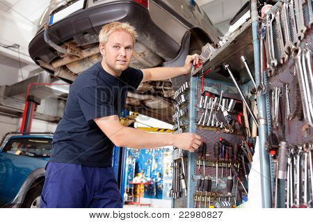 Mechanic standing beside tool chest, looking at the camera