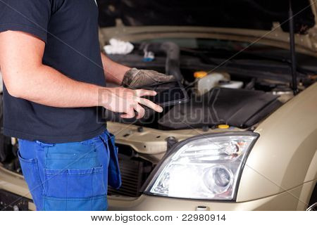 Detail of a mechanic with a digital tablet, car in background