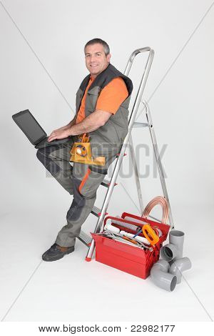 plumber sitting on stepladder with computer