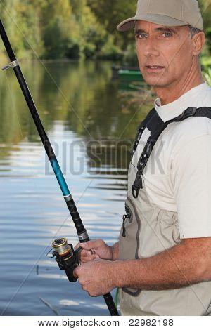 hombre de la edad de 50 años pescando en la orilla de un río