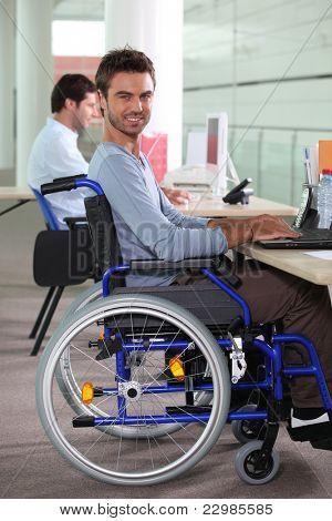Joven en silla de ruedas usando una computadora en el lugar de trabajo