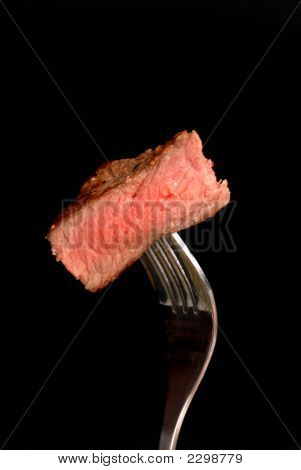 A Piece Of Grilled Ribeye Steak On A Fork