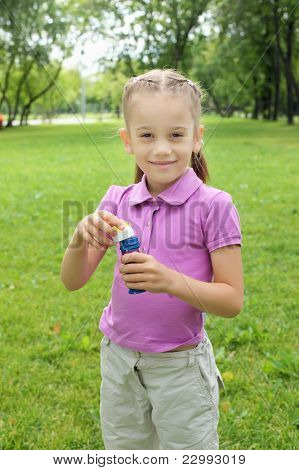Little girl in the park blowing bubbles