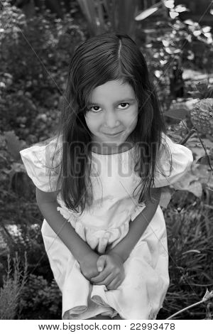 Hispanic girl crouched in garden