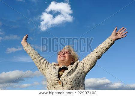 Feliz senhora Senior com mãos esticada contra o céu azul