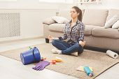 Woman Meditating, Sitting On Carpet While Cleaning Home In The Living-room, Copy Space. Housekeeping poster