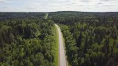 Aerial View Of White Car Driving On Country Road In Forest. Aerial View Flying Over Old Patched Two  poster