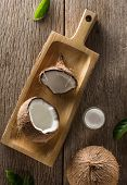 Creative Composition Coconut Half And Whole With Coconut Oil, Leaf And Coconut Products On Wooden Ta poster