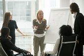 Female Team Leader Or Business Coach Gives Presentation To Multi-ethnic Partners Employees Group Exp poster