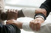 Four Multiracial Business People Holding Each Others Wrists, Diverse Partners Join Hands Together As poster