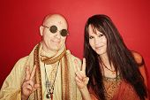 stock photo of swami  - Smiling guru with woman gestures peace sign over maroon background - JPG