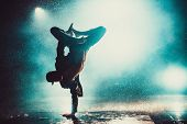 Young man break dancing in club with lights and water. Blue dramatic colors. poster