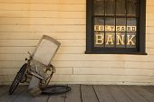 image of antique wheelchair  - Old broken wheel chair leans on the bank porch - JPG