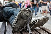 Homeless Man´s Sleeping In A Bench With Rotten And Dirty Feet Crossed With Destroyed Shoes From A Lo poster