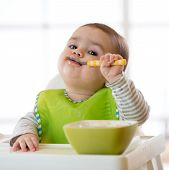 Baby Child Eats Healthy Food Himself With Spoon. Portrait Of Happy Kid Boy In High Chair. poster