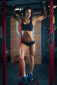 Fit Girl With Black Hair Wearing Black Short Top, Shorts And Gloves Standing With Horizontal Bar On  poster