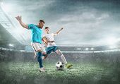 Soccer players on a football field in dynamic action at summer day under sky with clouds. Sporty man poster