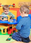 stock photo of nursery school child  - Two cute caucasian toddler playing in the kindergarten - JPG